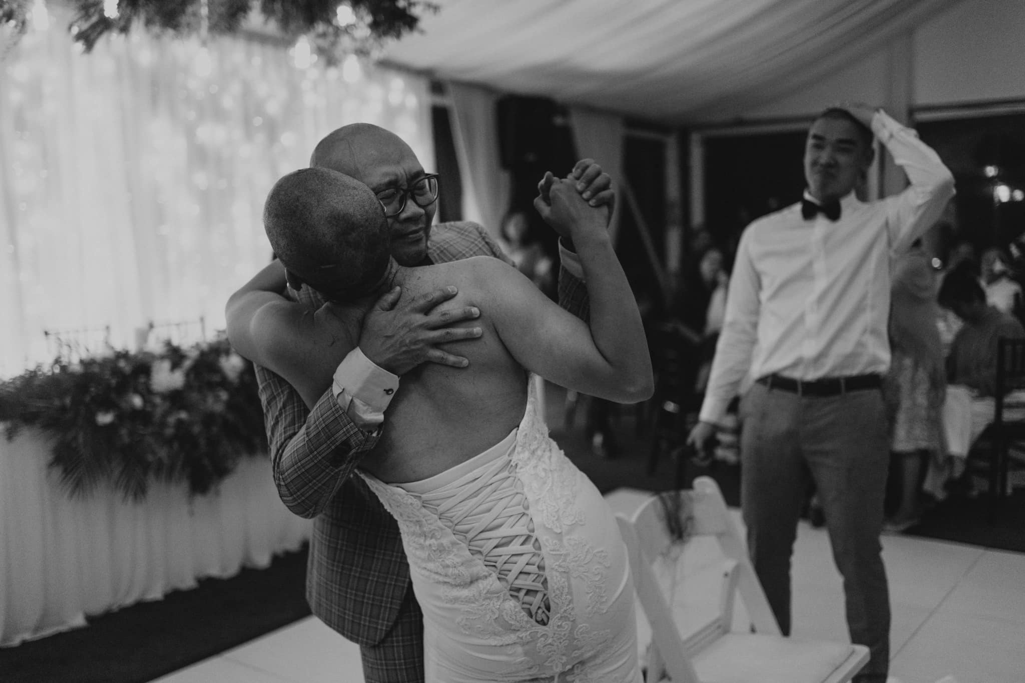 a bride suffering from cancer hugs her father on the dancefloor