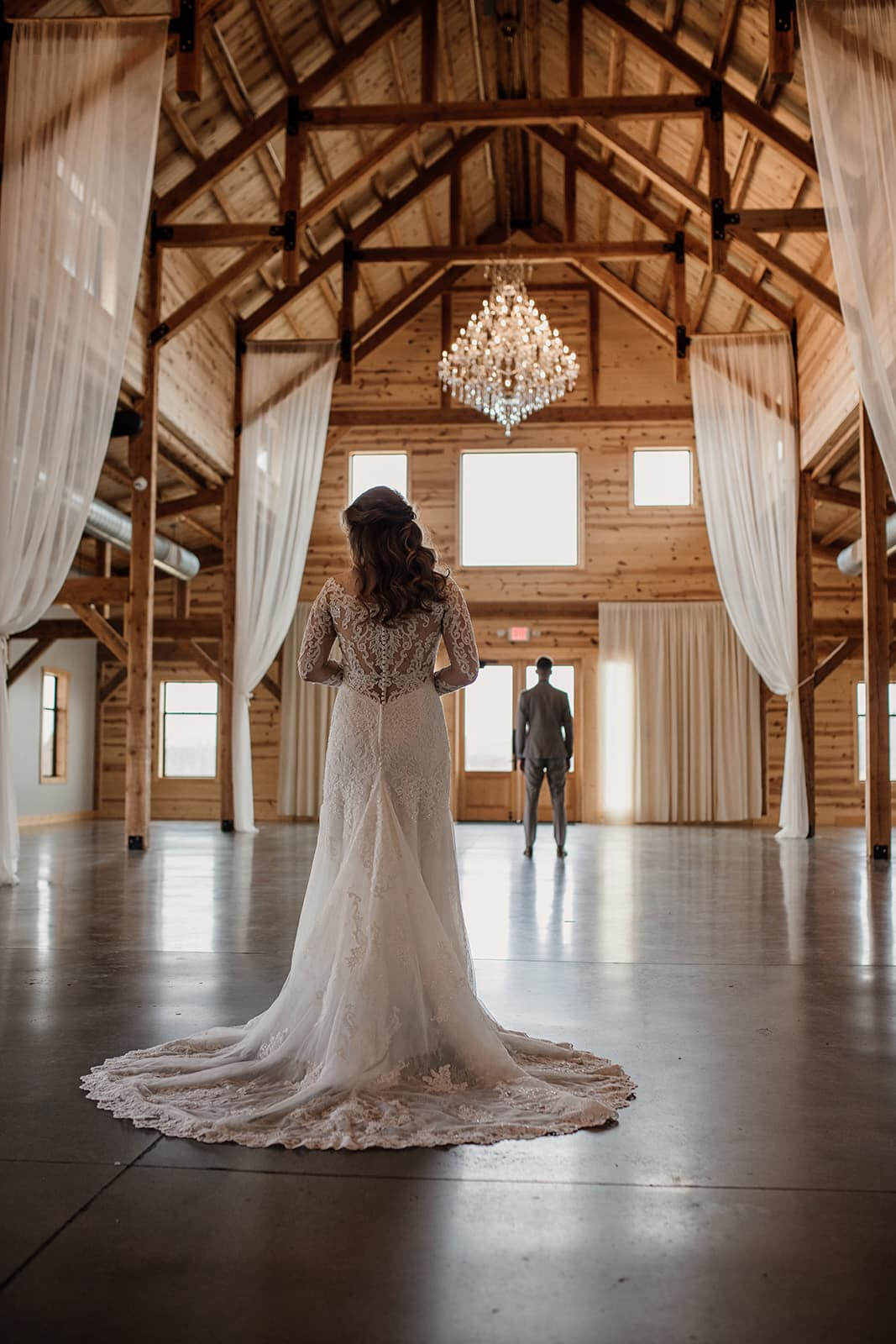 a groom waits for his bride in a wooden barn
