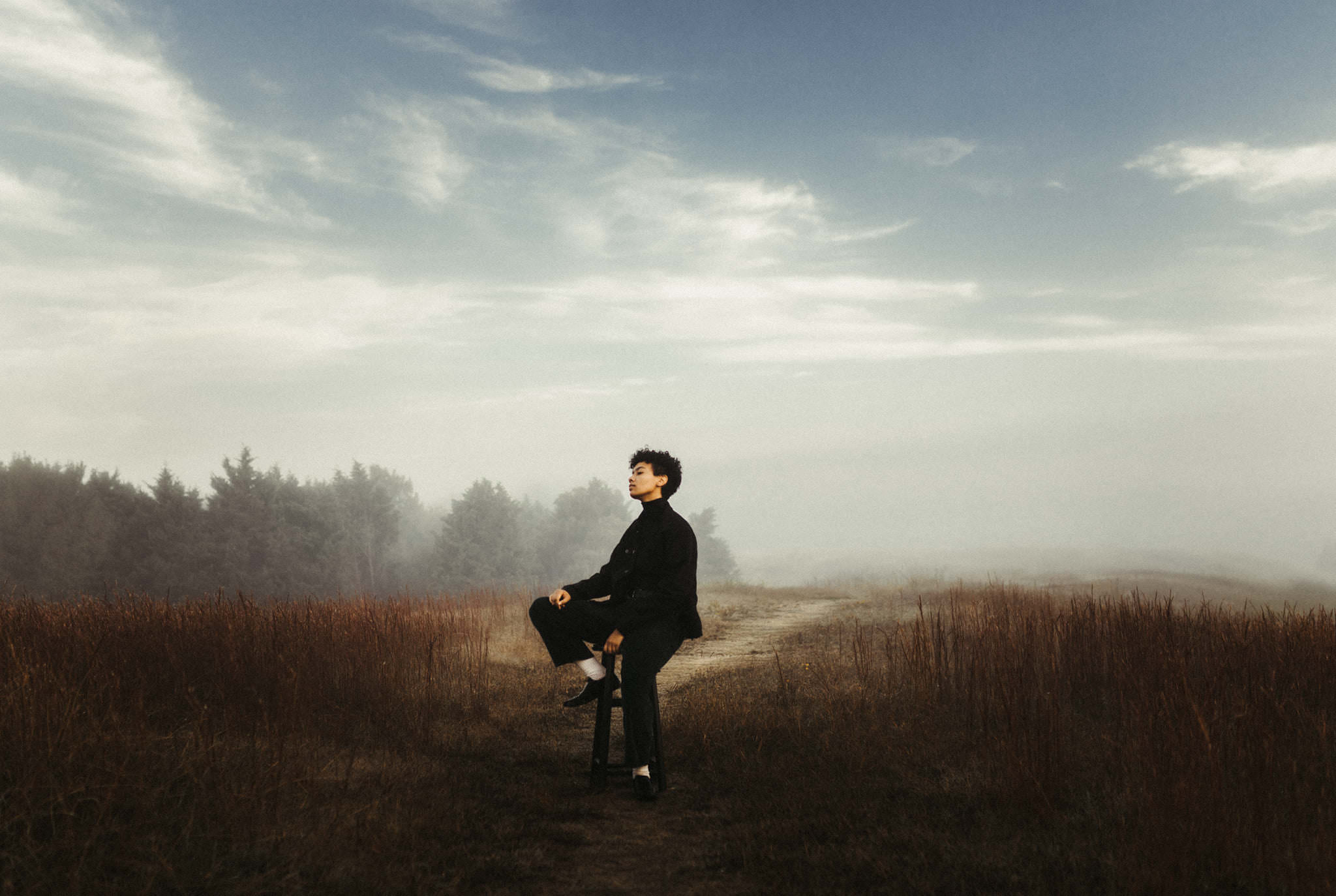a black woman is sitting on a barstool in a field on a cloudy day