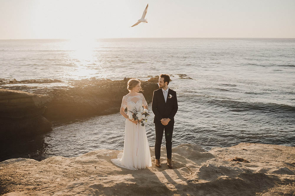 Wedding Couple standing at Sunset Cliffs with a seagull flying over them at sunset