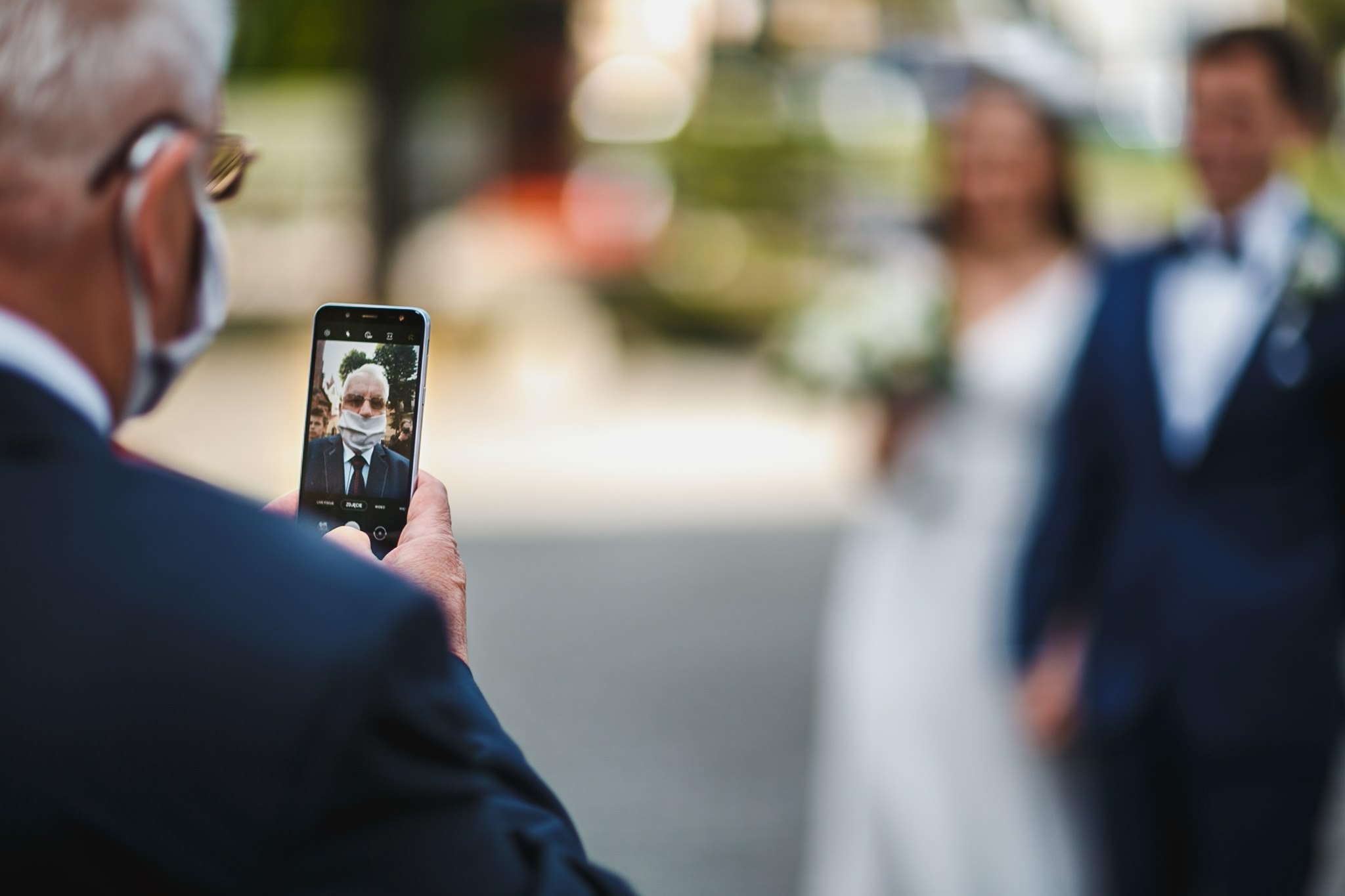 a grandfather wants to take a photo of the wedding couple with his phone but is accidentally taking a selfie