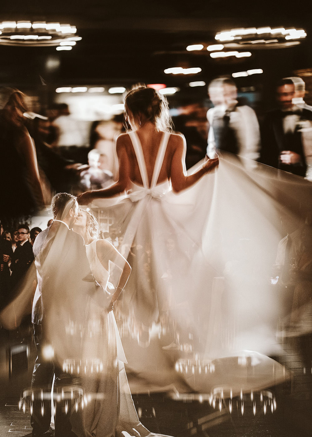 a double exposure of a bride dancing and the wedding couple kissing on the dancefloor