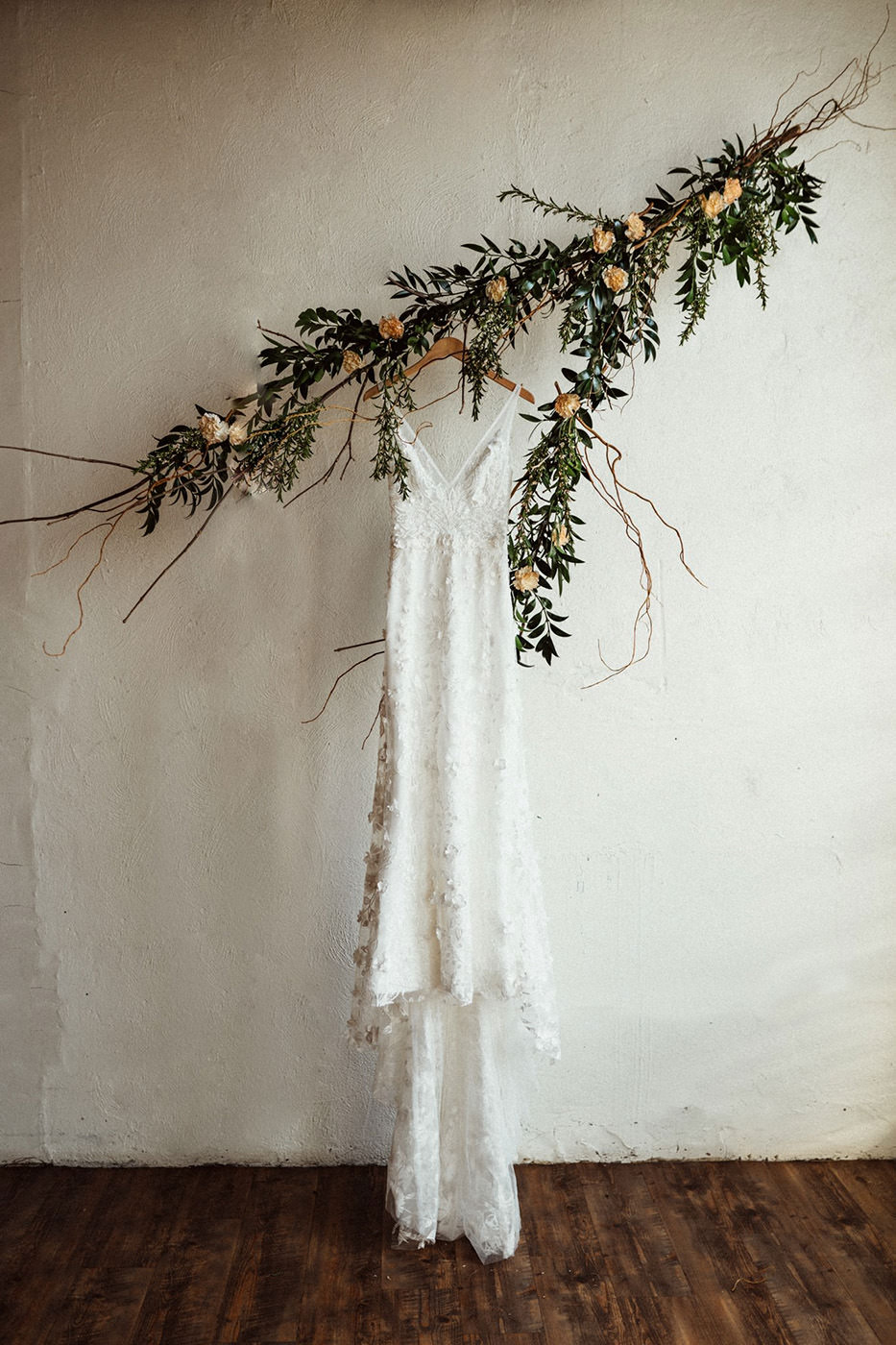 A stunning white wedding dress is hanging on a beautiful decorated stick in a room