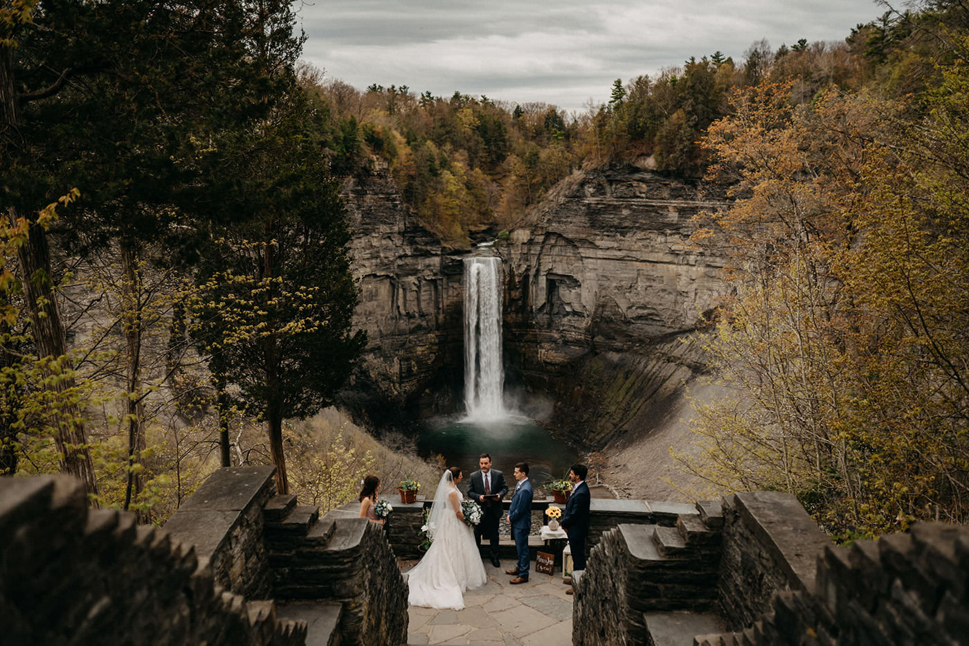 A wedding ceremony is taking place at a waterfall in the mountains