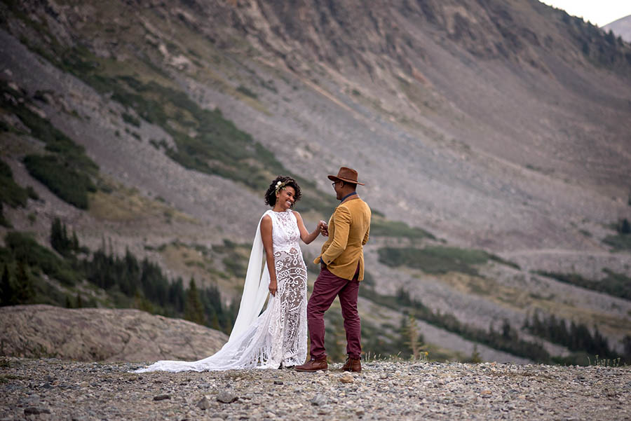 A wedding couple is holding hands and smiling at each other and are standing in Breckenridge.