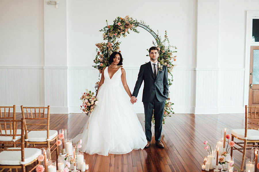 A wedding couple is holding hands and standing in front of an arch that is decorated with flowers at the business exchange.