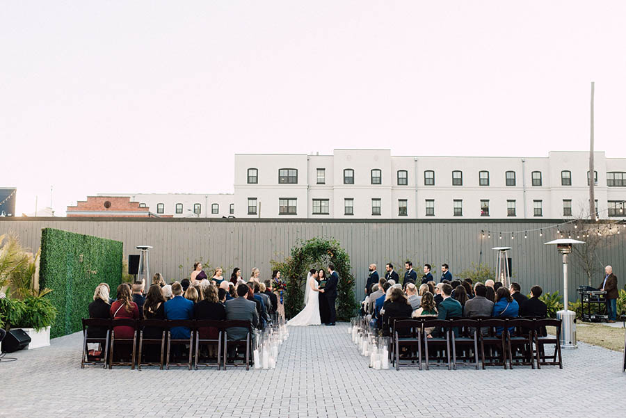 A couple is standing at the end of an aisle in-between next to their wedding guests in front of a building complex at the victory north.