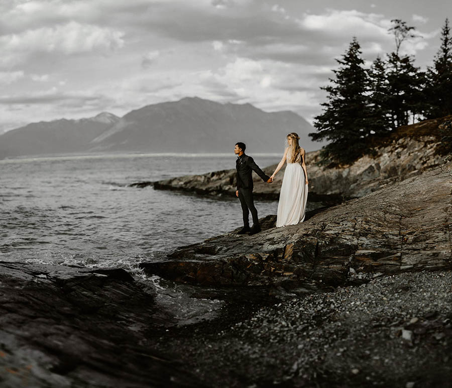 A wedding couple is standing next to the ocean on rocks and holding each others hand in Hope, Alaska.
