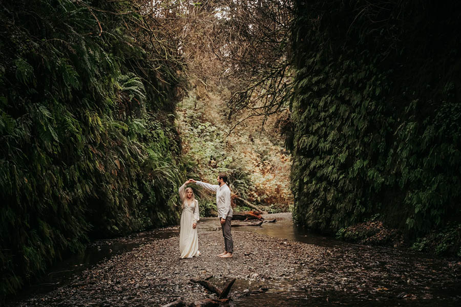 A wedding couple is dancing in the middle of the Fern Canyon in Northern California.