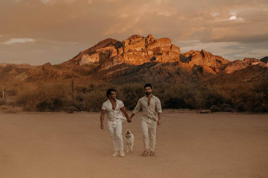 A wedding couple is holding hands and walking on a dusty area Iwrith a white dog in-between them in front of the Superstition Mountains in Arizona.