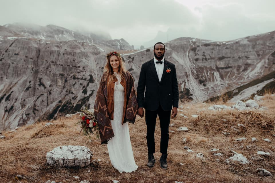 A wedding couple is standing on top of a mountain in the Dolomites.