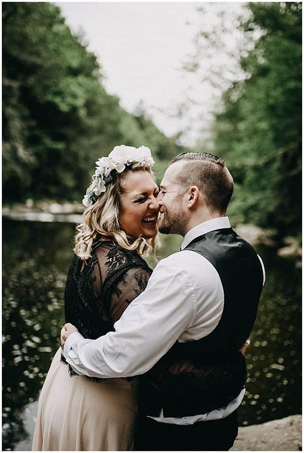 A wedding couple is holding each other and smiling at each other whilst standing in front of a lake in the Pocono Mountains.