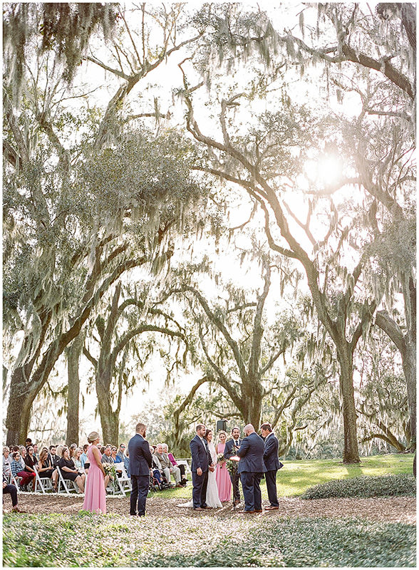 A wedding ceremony taking place in a garden full of trees, and the guests listen to the speech of the best man.