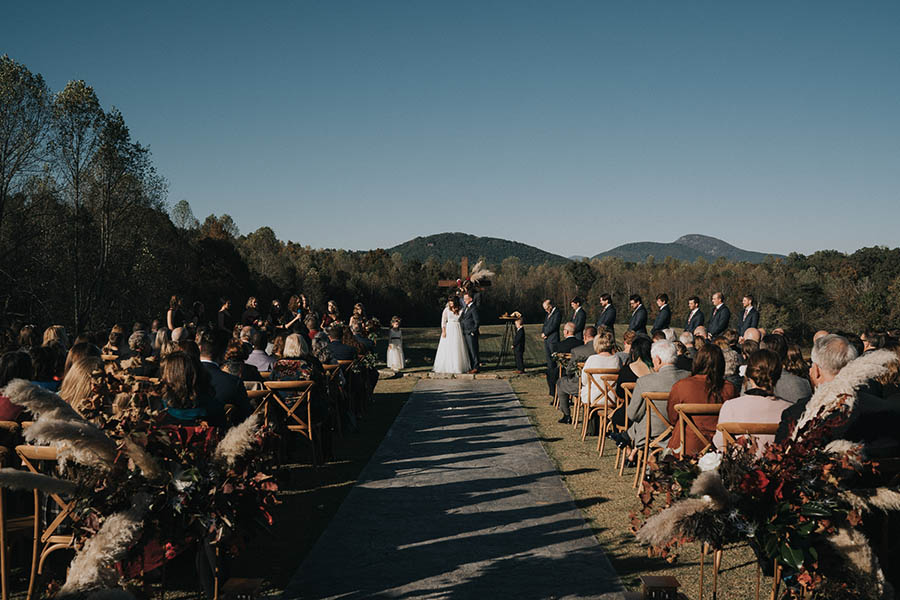 A wedding couple is standing at the end of an aisle at meadows at mossy creek and their wedding guests are to the right and left of them.