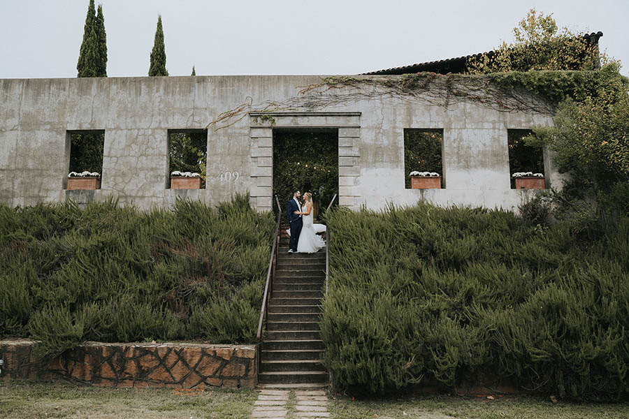 A wedding couple is standing on a staircase in front of a concrete building at the summerour studio.