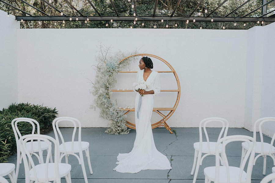 A bride is standing in front of a white wall and a wooden shelf at one of the best wedding venues in Georgia.