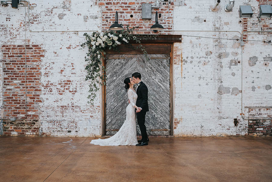 A wedding couple is kissing each other and standing in front of an old barn door and a brick wall in the engine room.