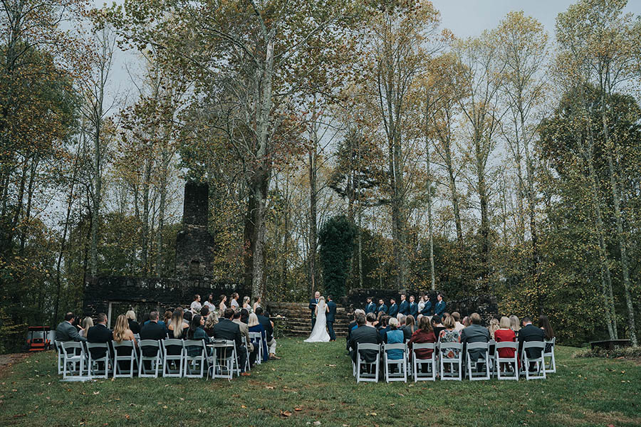 A wedding couple and their wedding guests are standing or sitting in front of the ruins at kellum valley.