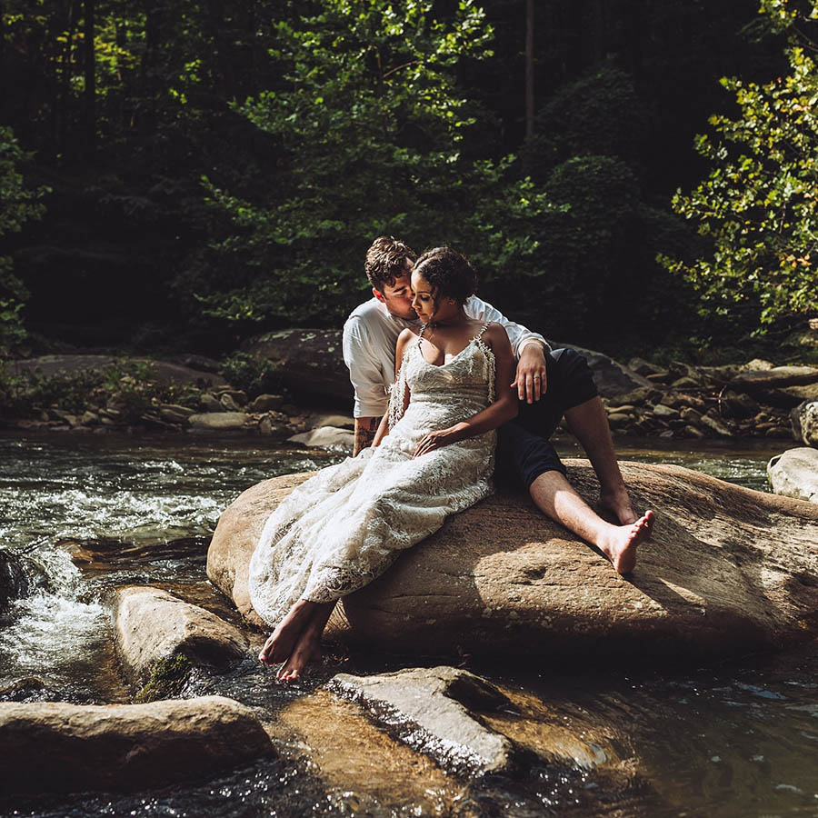 A wedding couple is sitting on a stone in a river in Asheville.