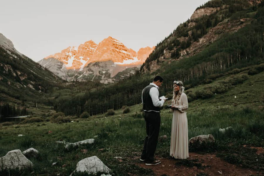 A wedding couple is reading their vows to each other and standing in a valley with the mountains and a forest behind them at the Maroon Bells.