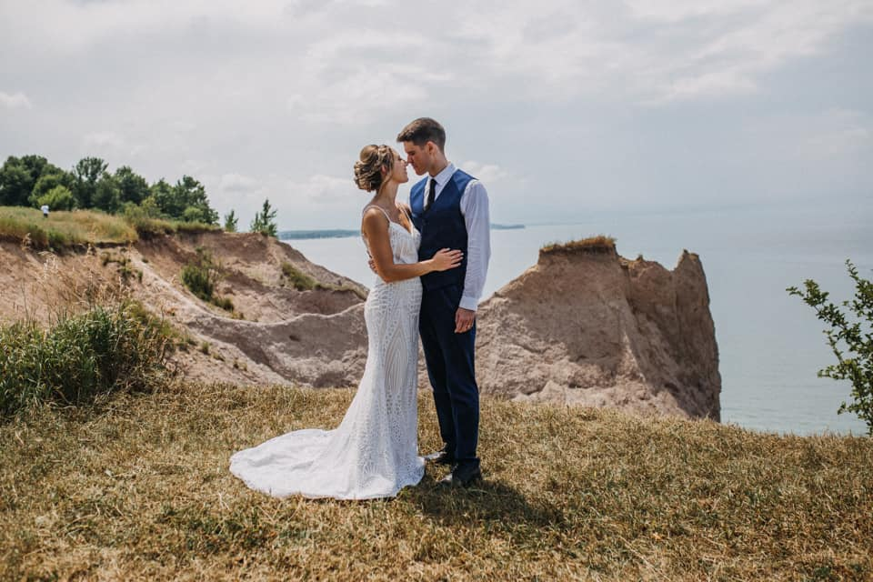 A wedding couple is standing in a field next to a cliff at the Chimney bluffs in Wolcott.