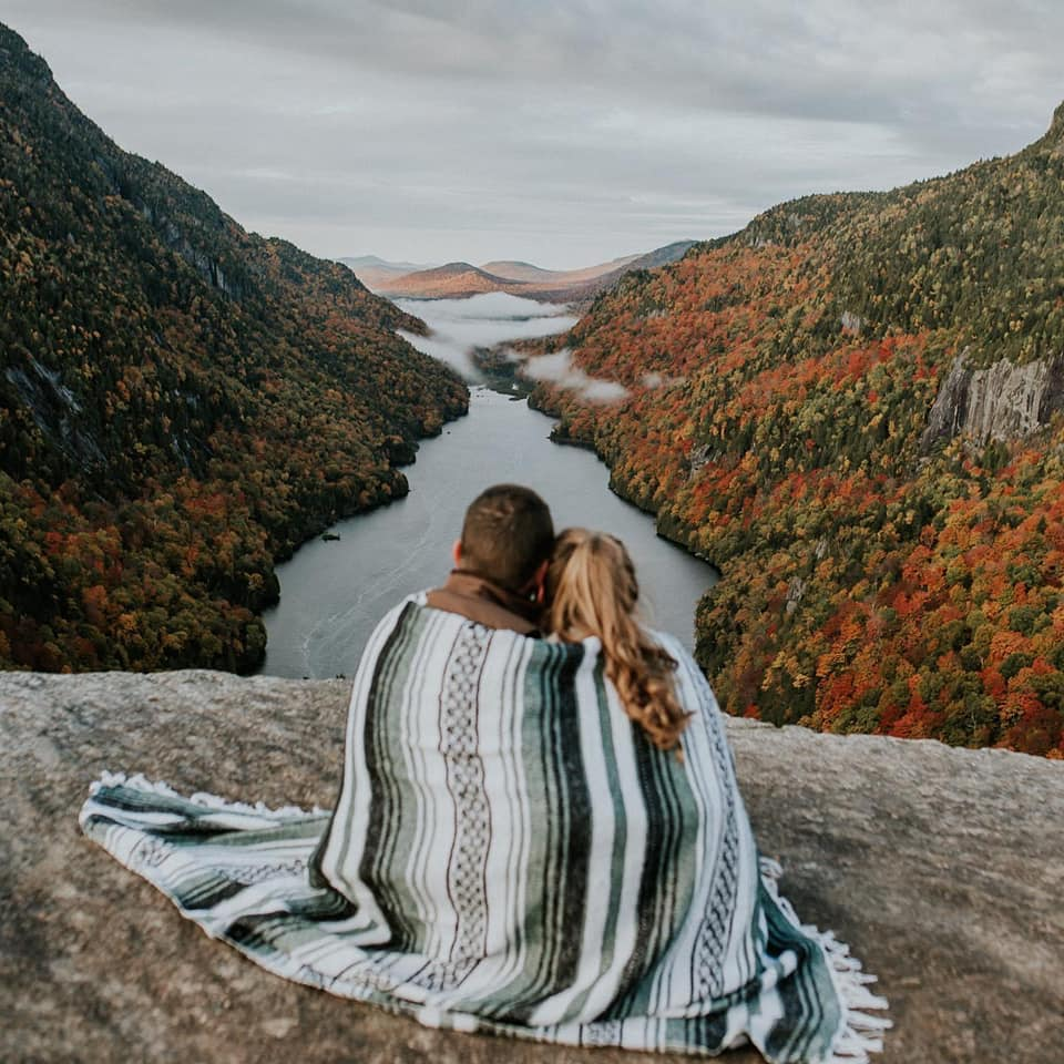 A couple is cuddling in a blanket and sitting on top of a mountain and looking to a lake in the valley at the Indianhead Mountain in the Adirondacks.