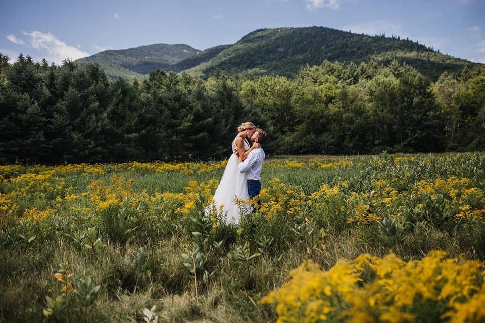 A wedding couple is kissing each other in a field of flowers in the Keene valley in Adirondacks.