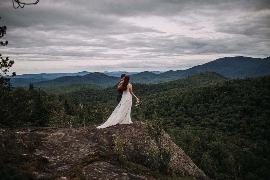 A wedding couple is standing at the edge of a mountain next to Lake George in New York.
