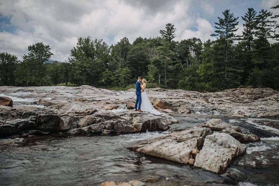 A wedding couple is holding each other and standing on rocks next to Lake Placid in New York.
