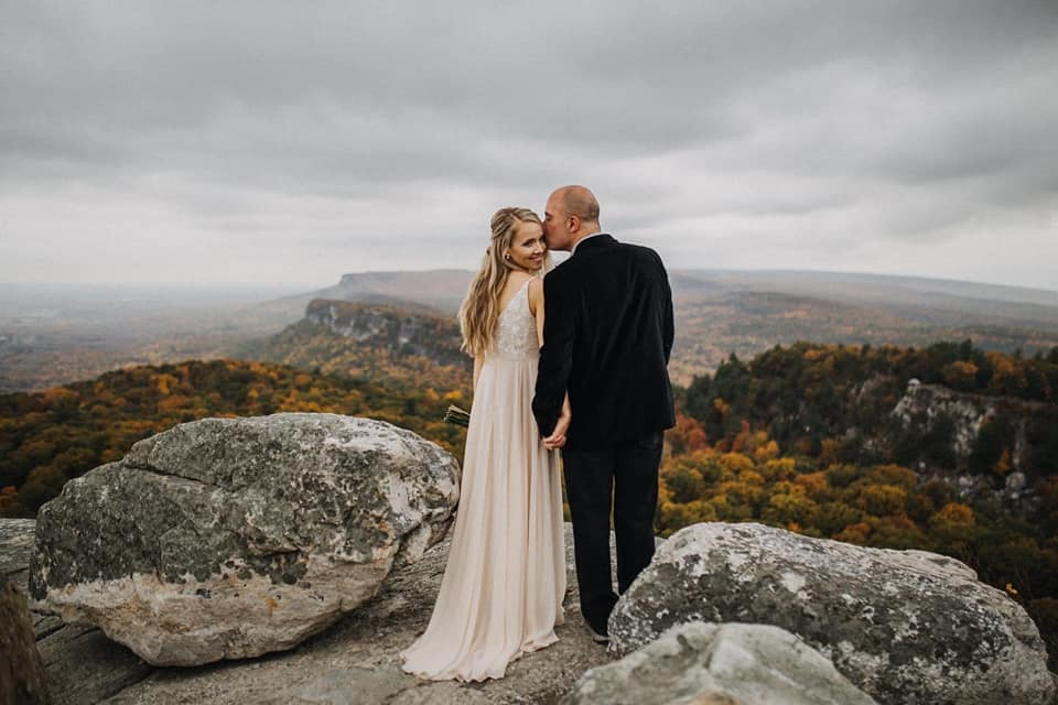 A wedding couple is holding hands and standing on top of the mountain at Mohonk Mountain House in New York.