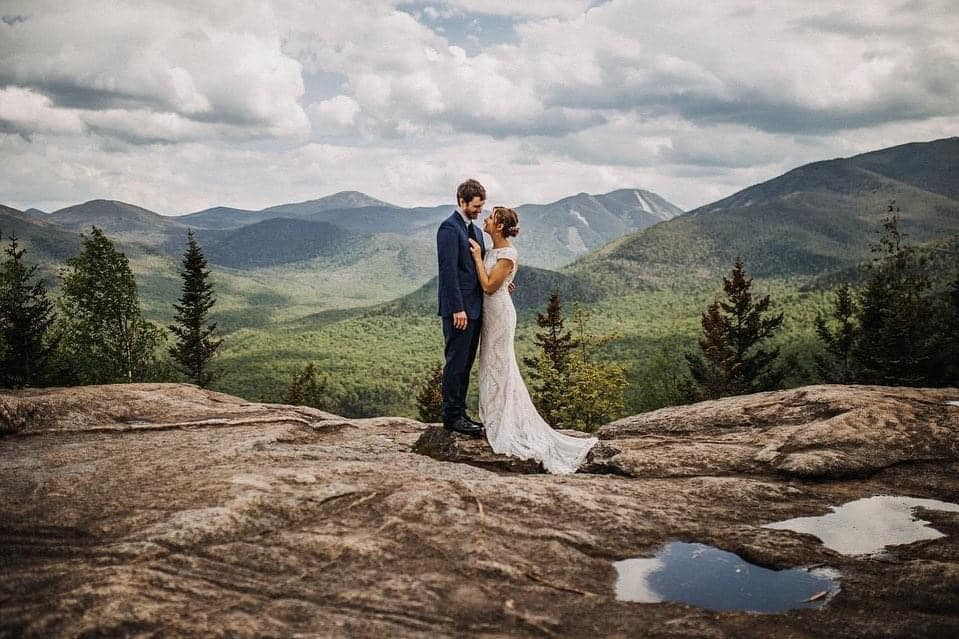 A wedding couple is standing on a mountain and looking at each other at Mt. Jo in the Adirondacks.
