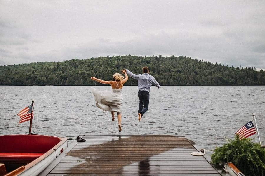 A wedding couple is jumping into the Saranac Lake in New York.