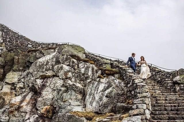 A wedding couple is walking down stairs at the Whiteface Mountain.
