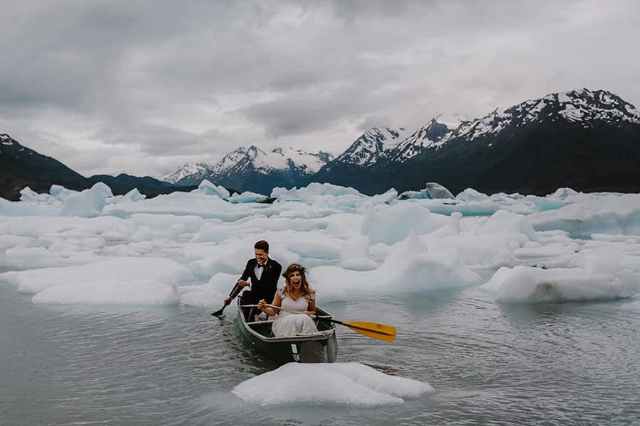 A wedding couple is in a rowboat in front massive ice blocks at the Church State Park in Alaska., photographed by a wedding photographer Alaska.