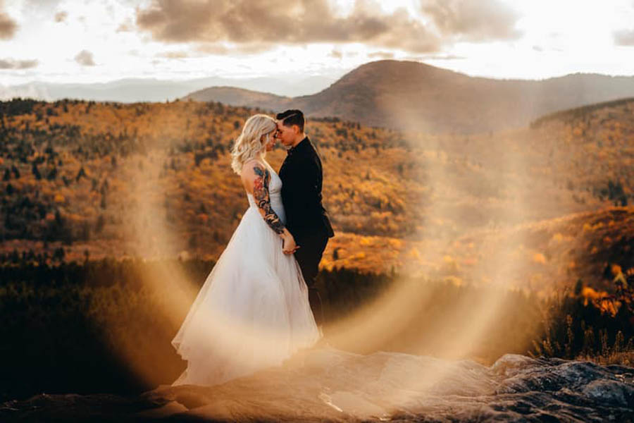 A wedding couple is standing on a flat rock and touching their foreheads and standing near a forest at the Black Balsam Knob in NC