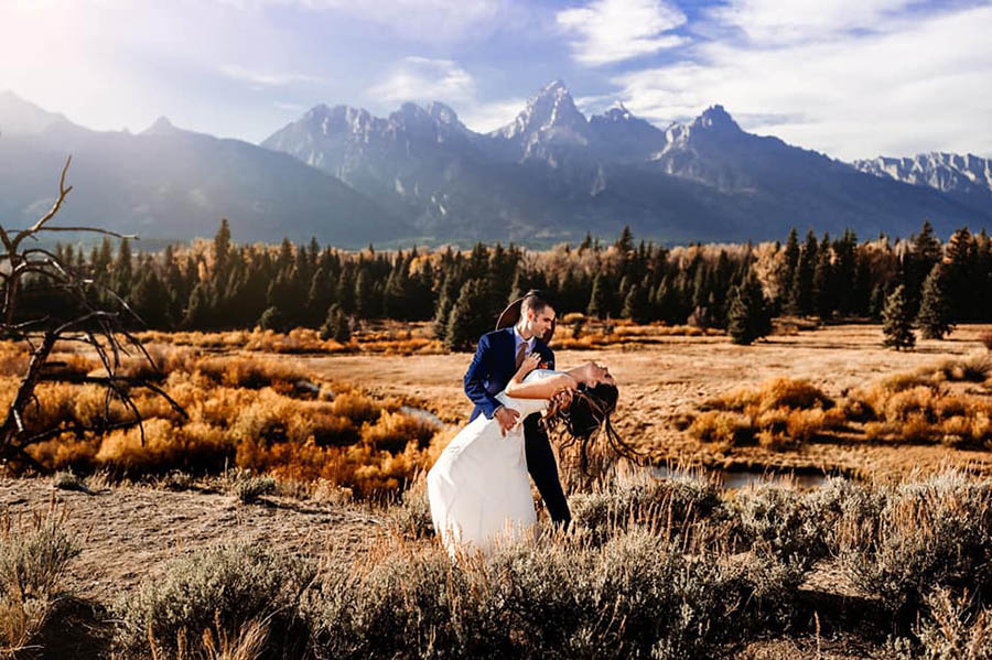 A groom is holding his bride and she is bending backwards and leaning into his arm and they are standing at the Grand Teton National Park.