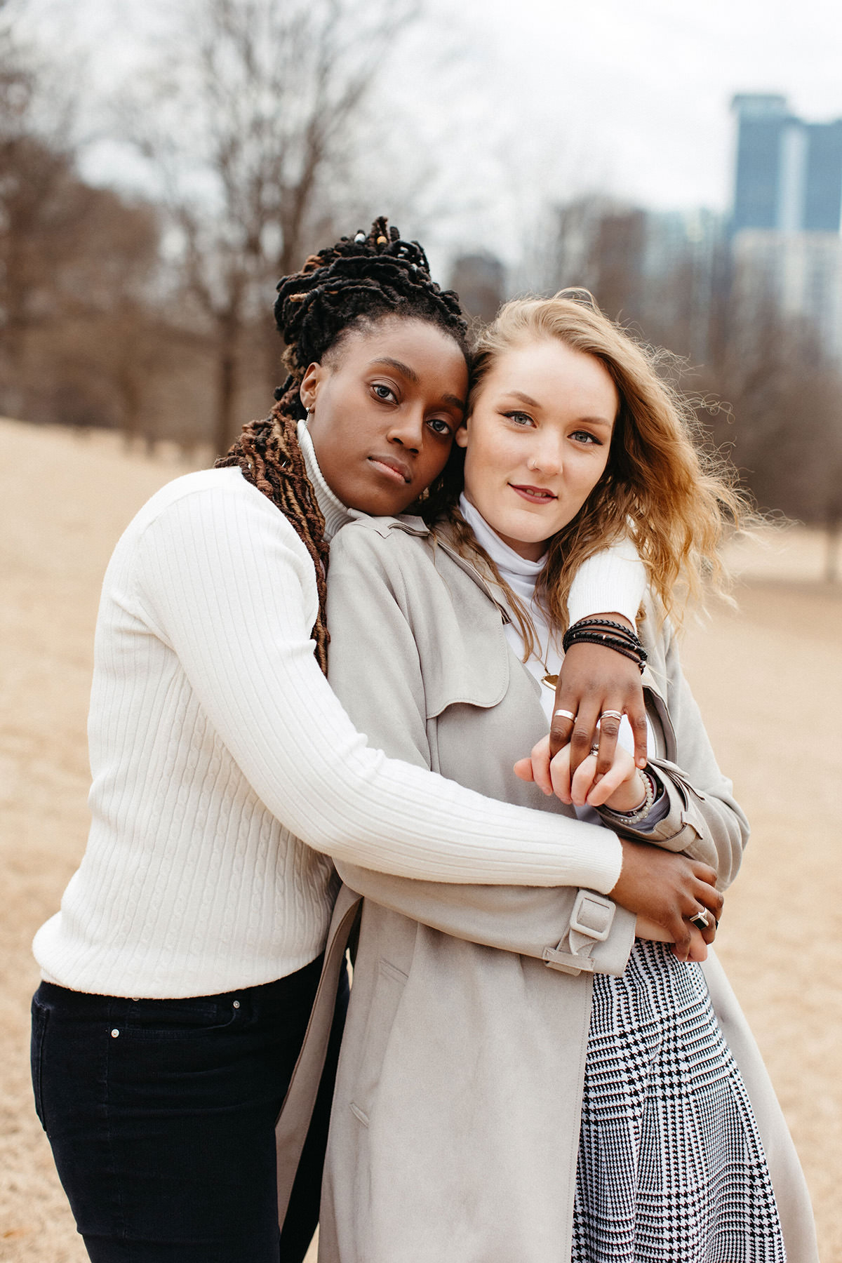 two women are embracing each other closely and are looking into the camera