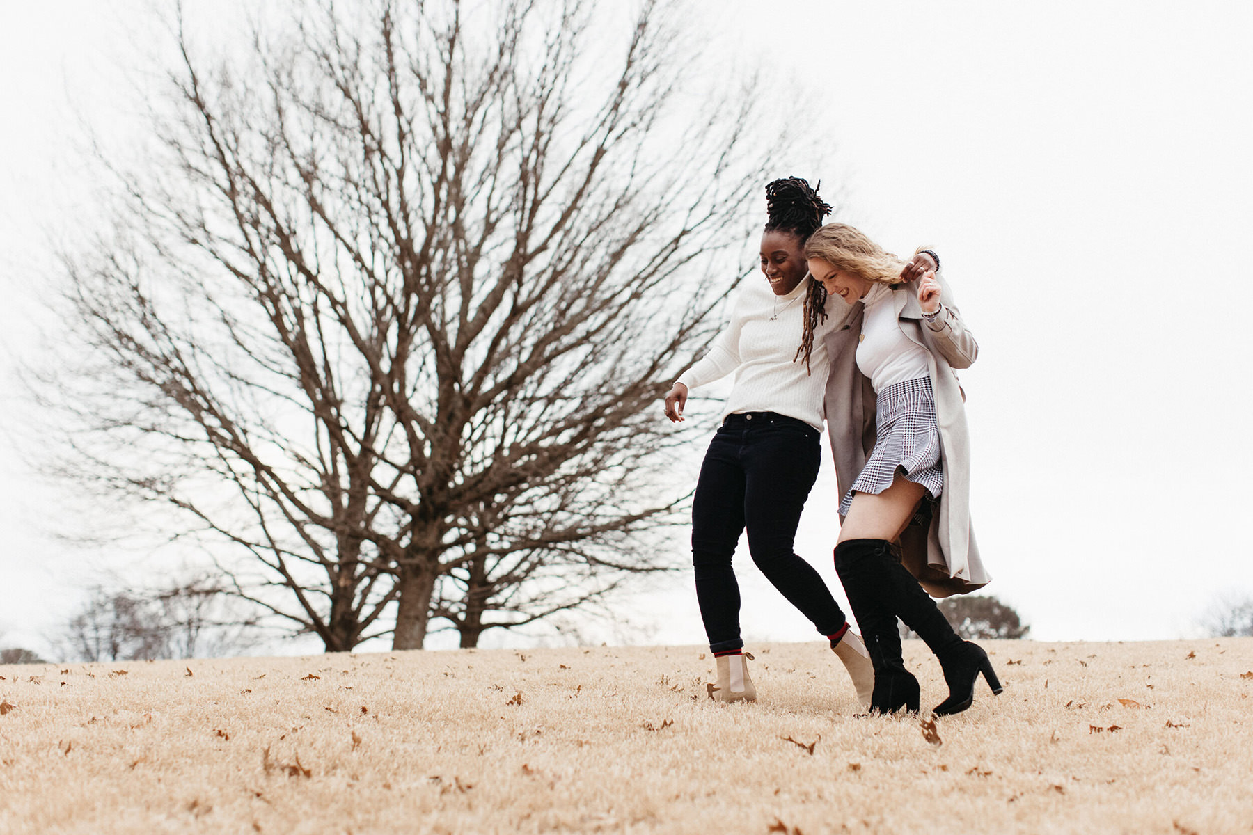 a couple is walking down a hill in a park during winter time