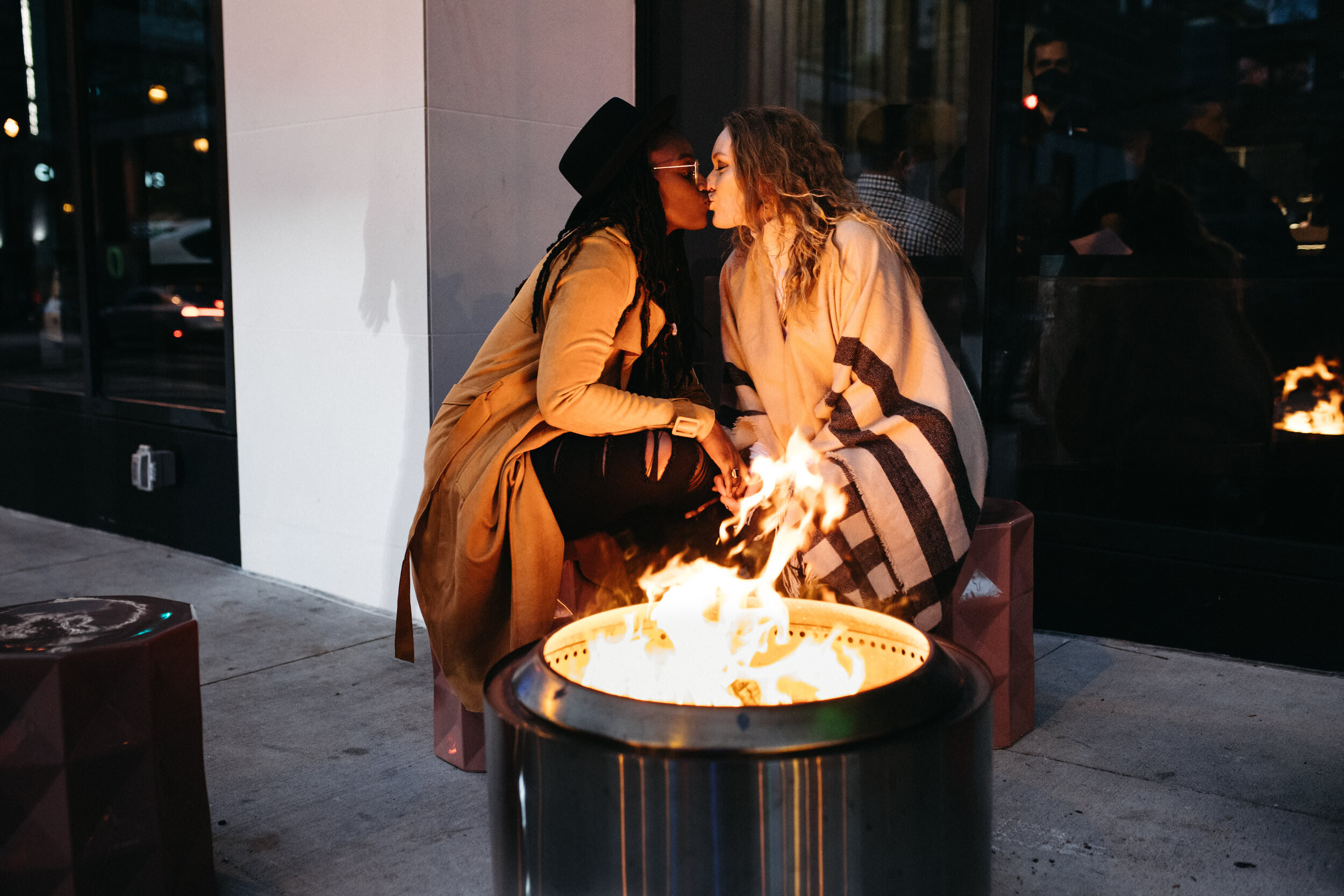 a lesbian couple kisses and sits next to a fire bin