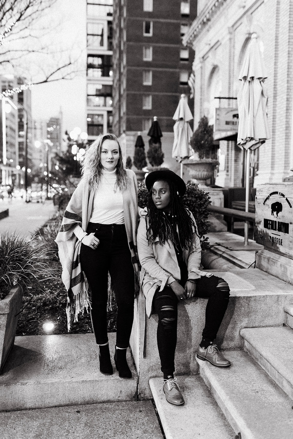 two women posing on stairs on a busy street