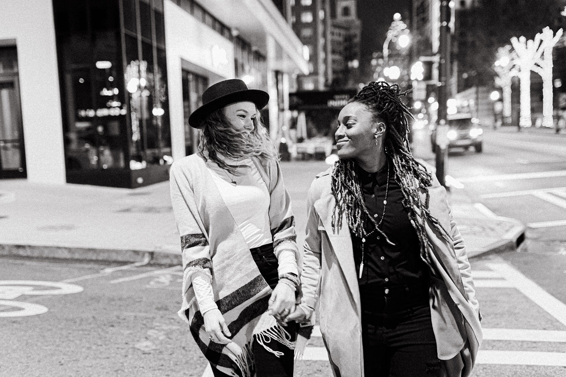 A couple looks at each other while crossing the street