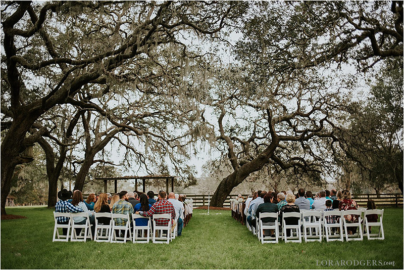 The wedding guests sit on white chairs underneath huge trees for the wedding ceremony to begin