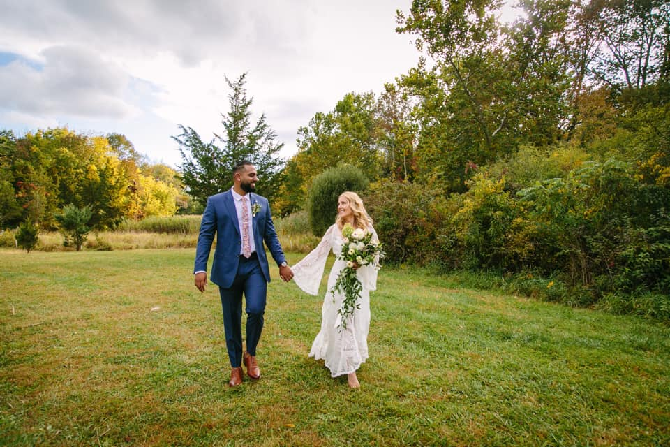A wedding couple is holding hands and smiling at each other at the Oasis Farm in New York.