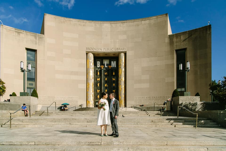A wedding couple is standing in front of the Brooklyn Public Library at the Prospect Park in New York.