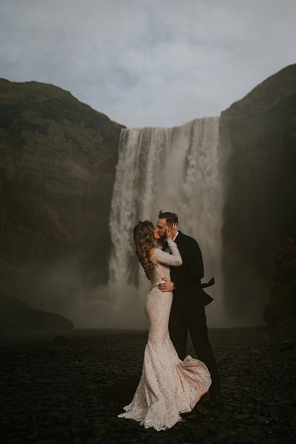 A wedding couple is kissing each other in front of a waterfall.