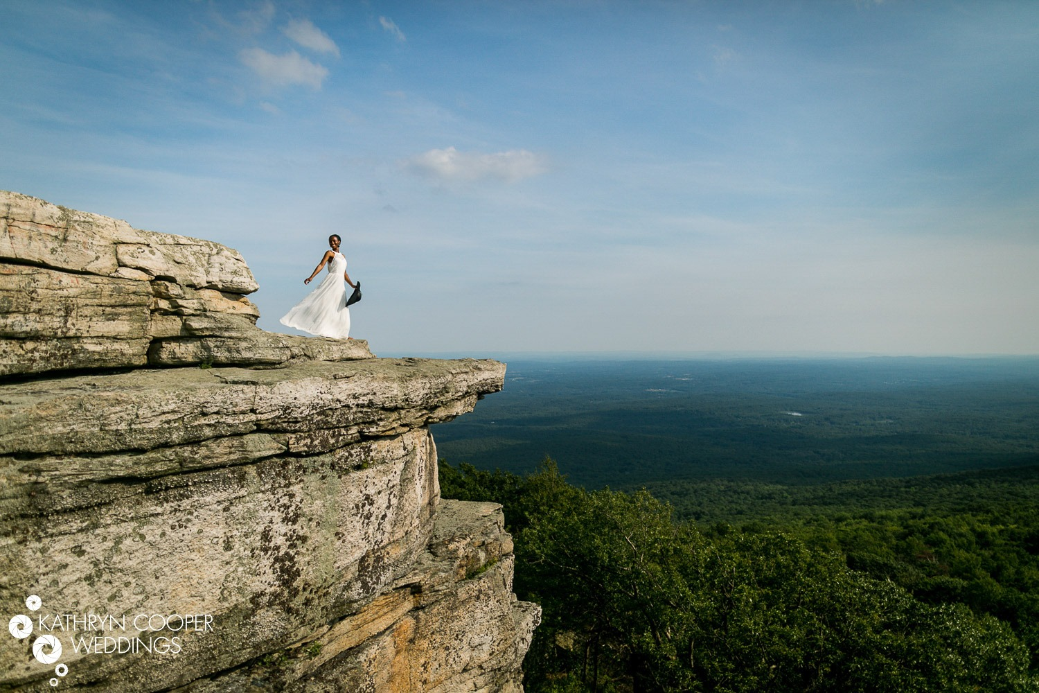 A bride is standing at the edge of a mountain at the Minnewaska State Park.