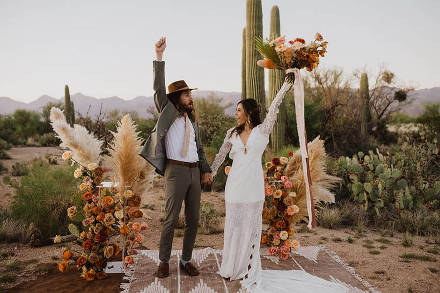A wedding couple is standing on a carpet in the middle of the Saguaro National Park and cheering.
