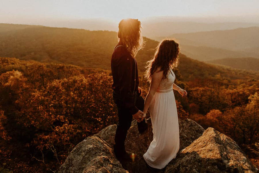 A wedding couple is holding hands and standing in the Shenandoah National Park in Virginia.