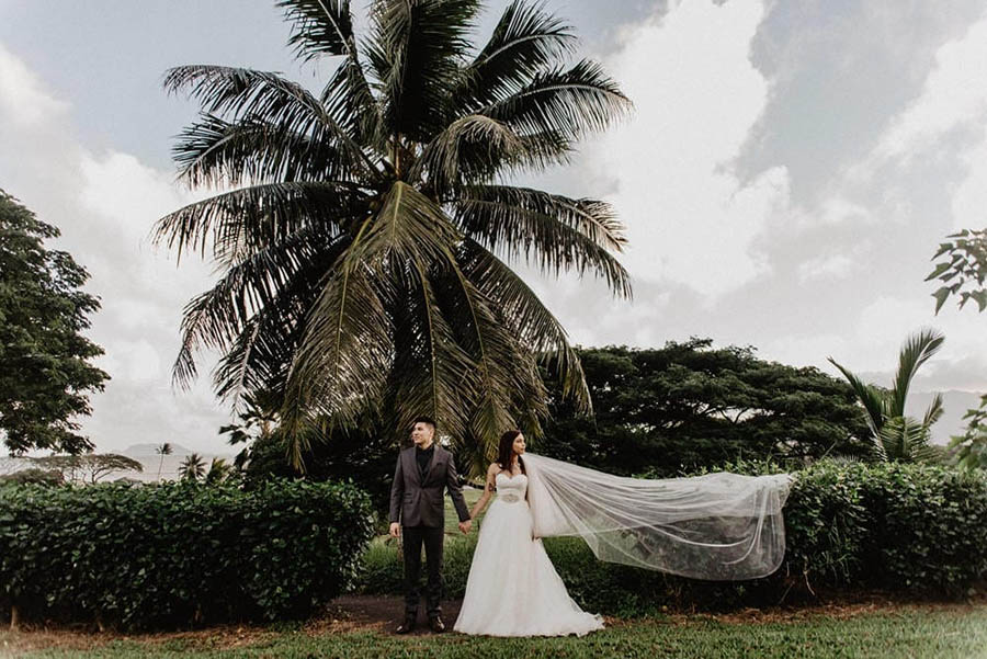 A wedding couple is holding hands and looking away from each other in the opposite direction and they are standing in front of a garden in Oahu.