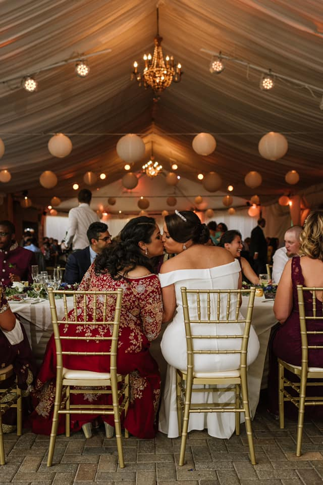 Two brides are kissing each other and sitting on chairs in the Piedmont Garden Tent.